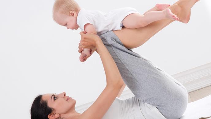 赤ちゃんと2人でエクササイズをするママ