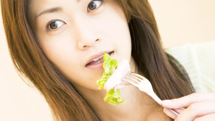 エコー写真を見ながらサラダを食べる妊婦