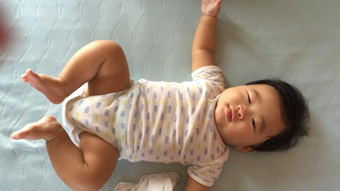 布団に大の字で寝る赤ちゃん