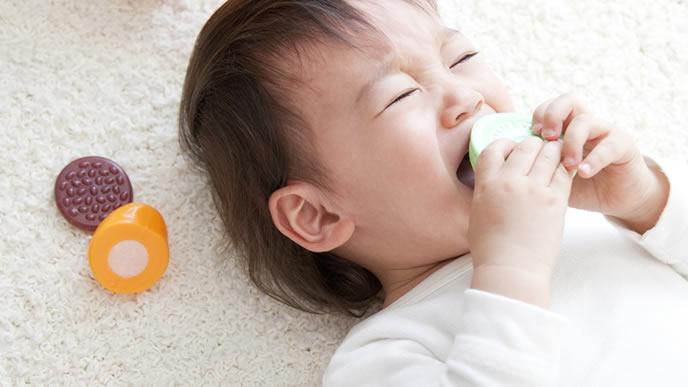 泣きじゃくりおもちゃを口にしようとする赤ちゃん