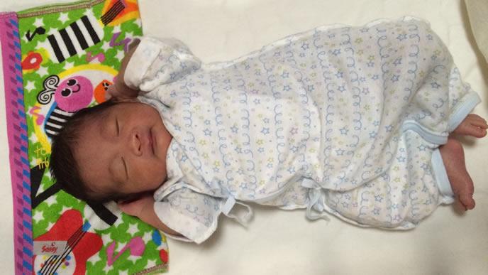 頭を抱えて熟睡する生後1ヶ月の赤ちゃん