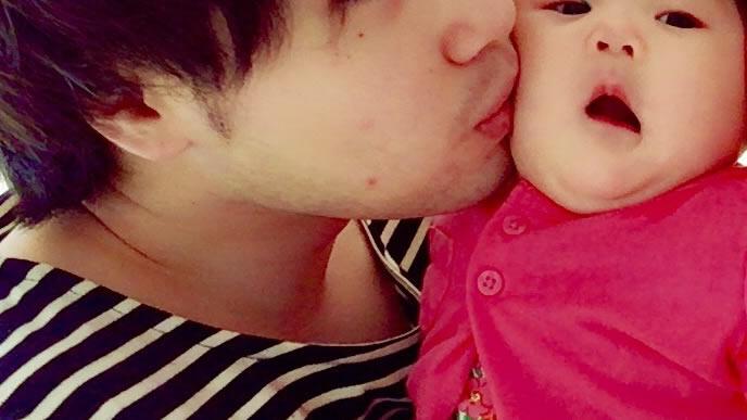 パパにキスされ驚きの表情になる赤ちゃん
