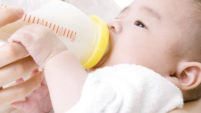 ミルクを飲み残さないように赤ちゃんに与えるママ
