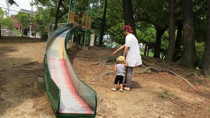 パパと一緒に滑り台に乗ろうとする男の子
