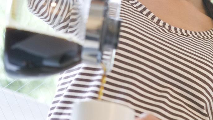 朝食のためのコーヒーを注ぐ妊婦