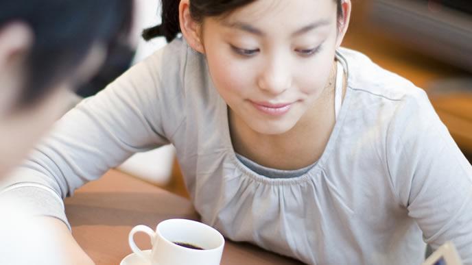 コーヒーを飲みつつパソコンを覗く女性