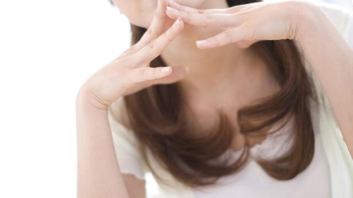 手を組み考え事をする女性
