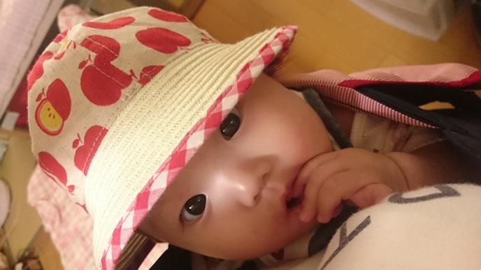 お気に入りの帽子をかぶりママに話しかけようとする赤ちゃん