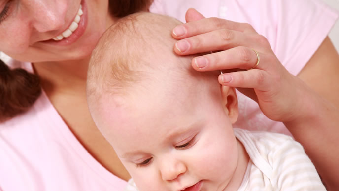 後追いする赤ちゃんを優しくなでるママ