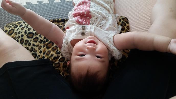 ママの間に入ってご機嫌な生後6ヶ月の赤ちゃん