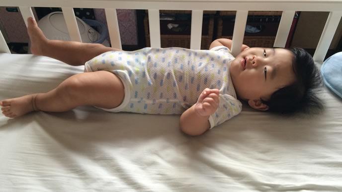 薄目を開けママを見つめる寝たふり中の赤ちゃん