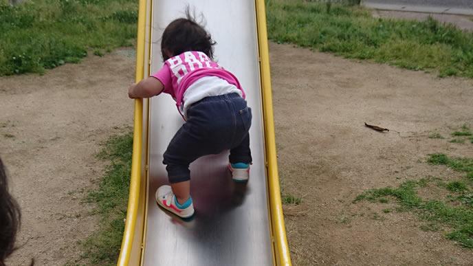 公園の滑り台を使い全力で遊ぶ女の子