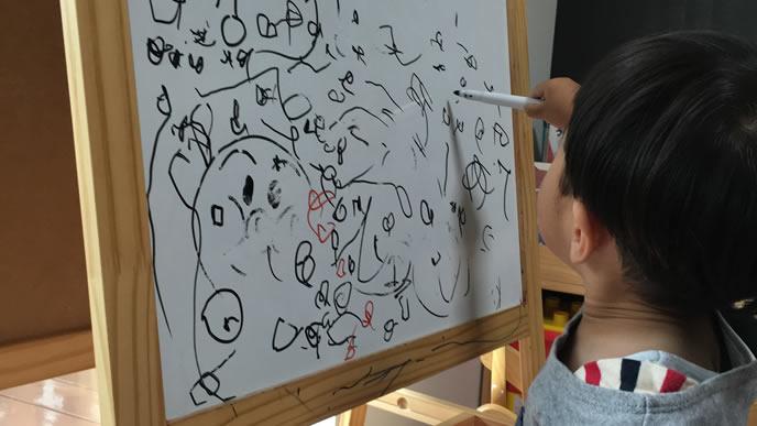 ホワイトボードで落書きする卒乳間近の赤ちゃん