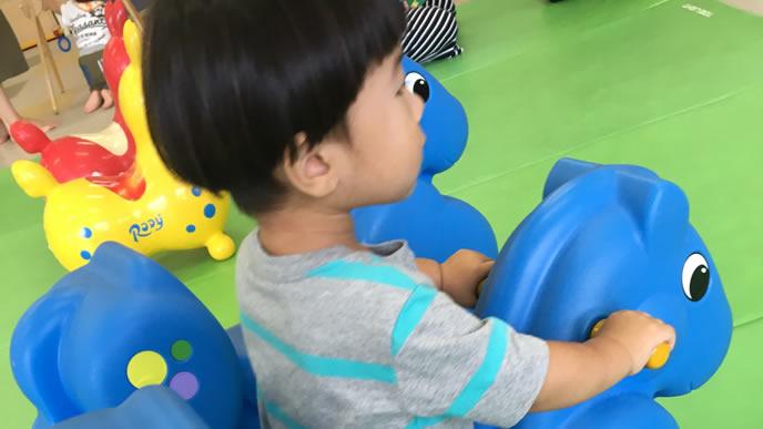 馬に乗り遠くを見つめる赤ちゃん