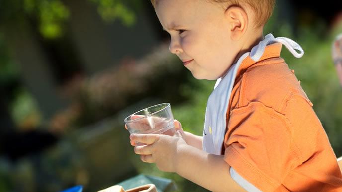 喉を潤すための水を飲む赤ちゃん