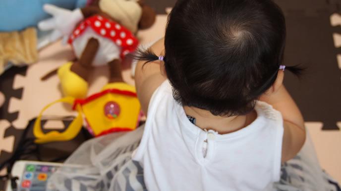 赤ちゃんの様子を後ろから観察するママ