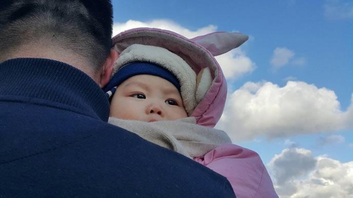 納得できない表情のパパ見知り中の赤ちゃん