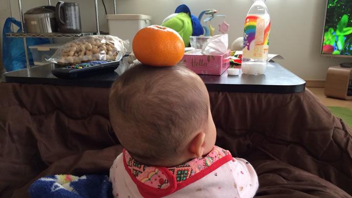 頭にみかんを乗せた生後8ヶ月の赤ちゃん