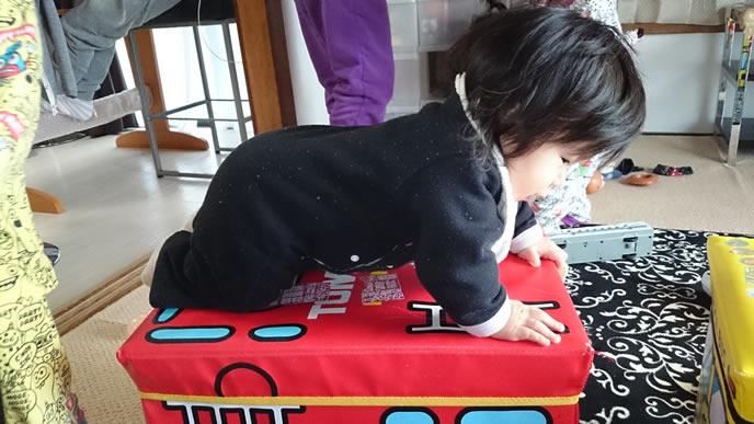 おもちゃの上でハイハイをする生後12ヶ月の赤ちゃん