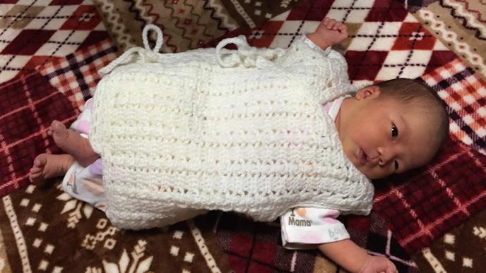 毛糸のおくるみに包まれる生後1ヶ月の赤ちゃん