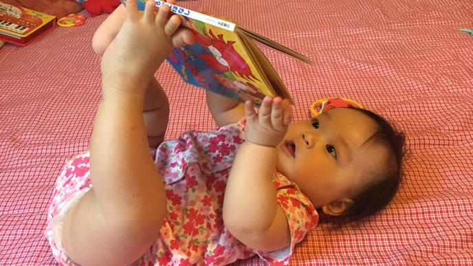自分で絵本を見る赤ちゃん