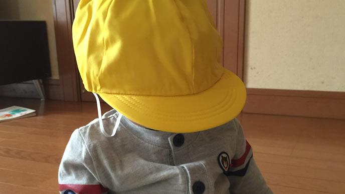 帽子を深くかぶり照れる赤ちゃん
