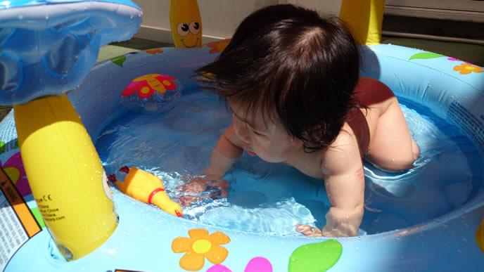 暑い夏にビニールプールに入る赤ちゃん