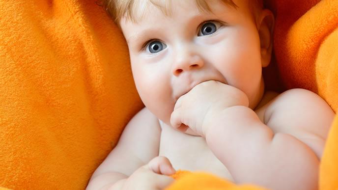 指だけでなく拳まで口に入れようとする赤ちゃん