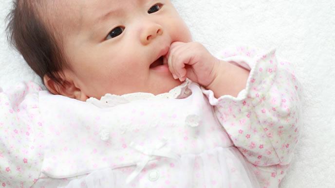 ママを遠目で見つめながら指しゃぶりをする赤ちゃん