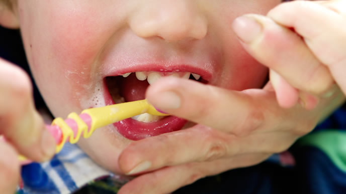 ママに歯磨きしてもらう赤ちゃん