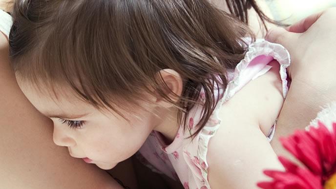 ママに抱っこしてもらう少し眠たい赤ちゃん