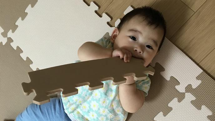 床のマットを噛みながらカメラを見る赤ちゃん