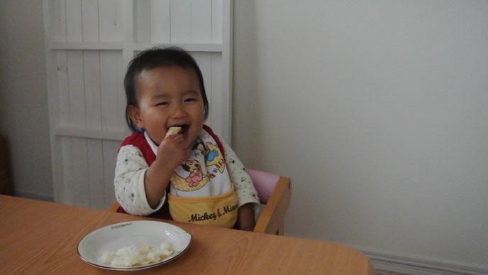 離乳食を手づかみで食べる笑顔の女の子