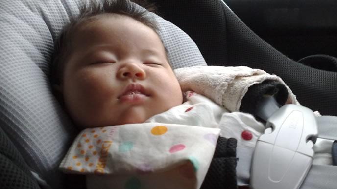 ベビーシートの上で寝言泣きをしている赤ちゃん