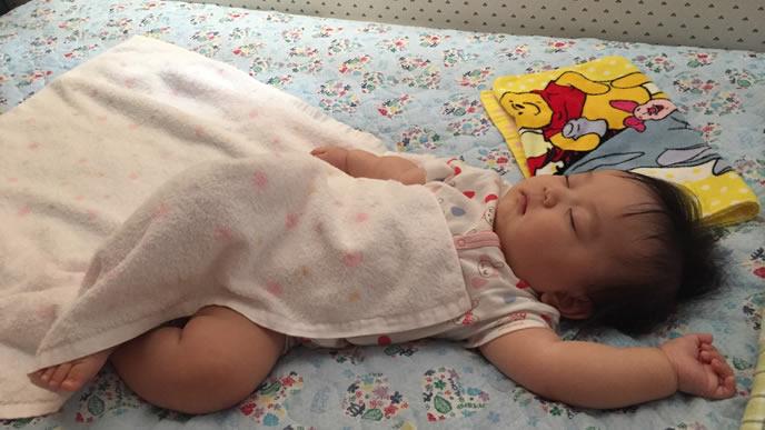 タオルを布団にして熟睡する赤ちゃん