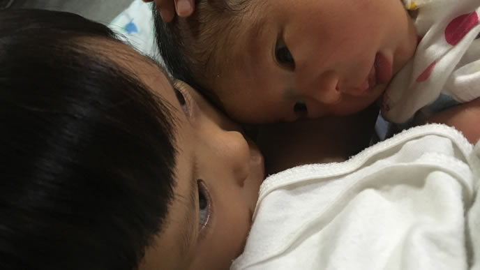 兄と一緒に寝そうな赤ちゃん