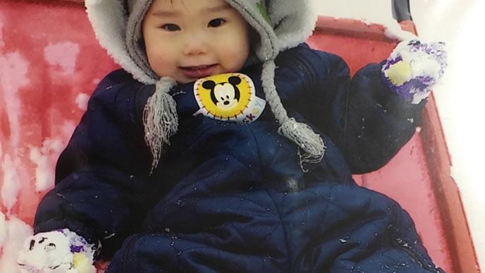 初めての雪遊びを楽しむ男の子