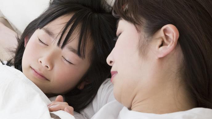 寝言泣きする子供を見守るママ