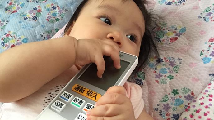 エアコンのリモコンを食べるぱっちり二重の赤ちゃん