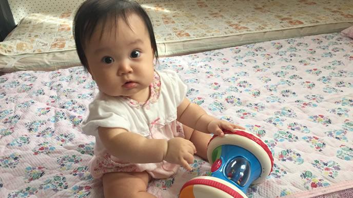 一人遊び中のキョトン顔の赤ちゃん