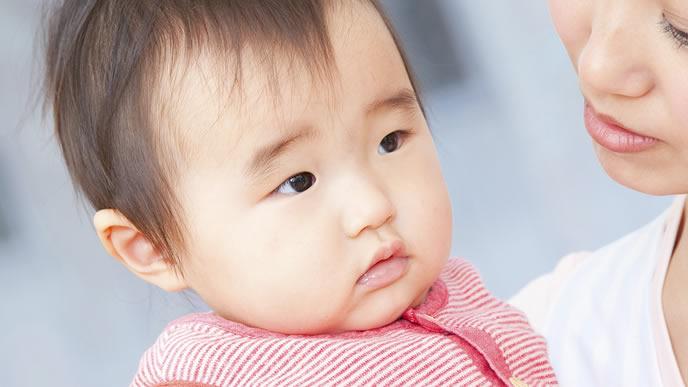 険しい表情で遠くを見つめる赤ちゃん