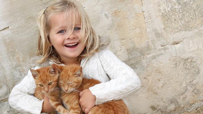 女の子に抱えられ迷惑そうな猫