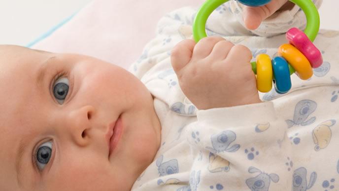 プラスチックのラトルで遊ぶ赤ちゃん