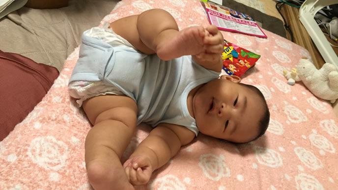 布団の上にコロンと転がる赤ちゃん