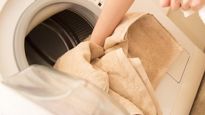 布おむつと一緒にタオルを洗濯するママ