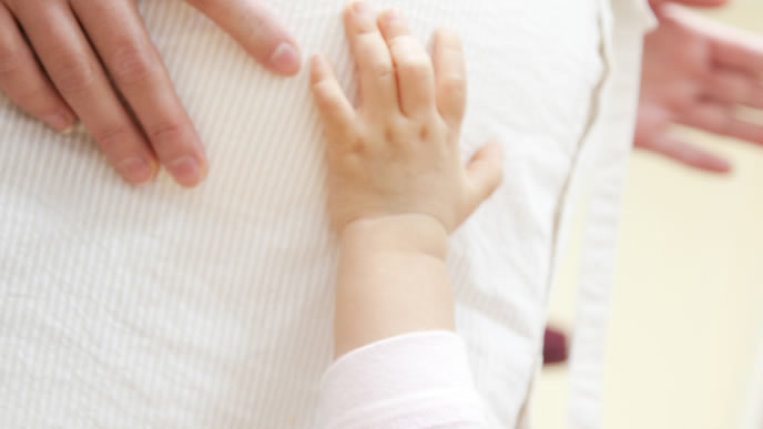 ママのお腹に手をあて胎動を感じる赤ちゃん