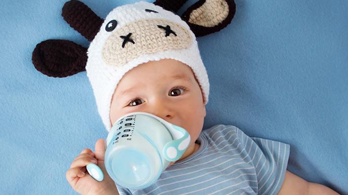 ベビーマグでミルクを飲む赤ちゃん