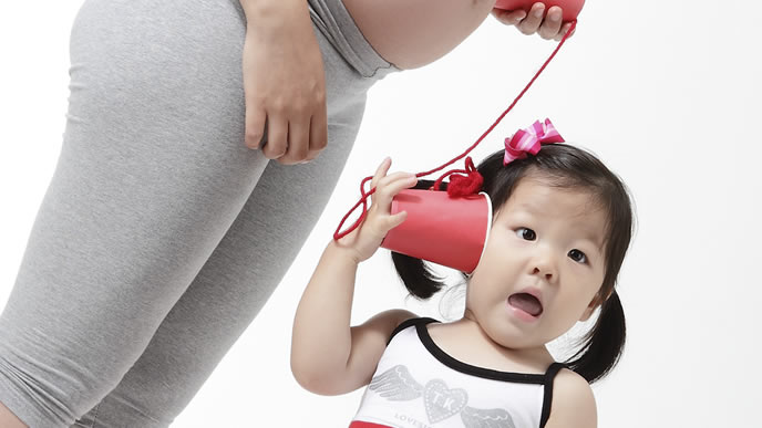 ママのお腹の赤ちゃんと糸電話する女の子