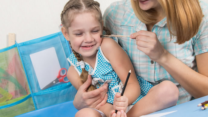 筆でママと仲良く遊ぶ女の子