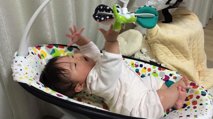 バウンサーに取り付けられたメリーで遊ぶ赤ちゃん